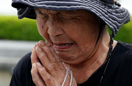 Японская женщина молится у памятника жертвам ядерного удара в Хиросиме.