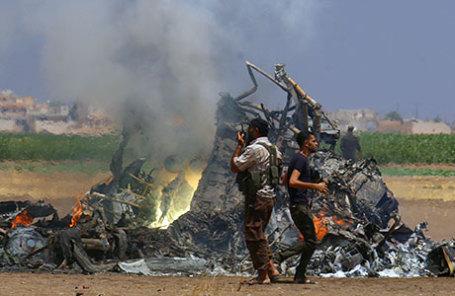 Мужчины осматривают обломки российского вертолета, который был сбит повстанцами Идлиб.