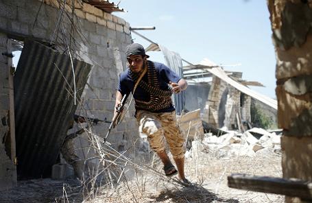 Ливийский боец бежит в укрытие во время сражения с запрещенным «Исламским государством».