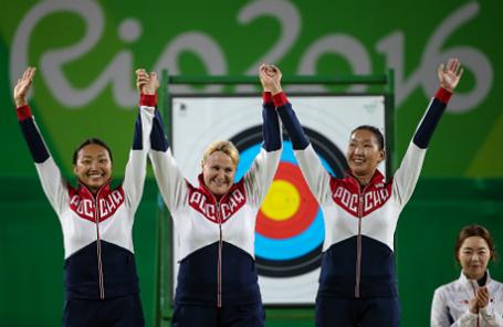Российские спортсменки Туяна Дашидоржиева, Ксения Перова и Инна Степанова (слева направо), завоевавшие серебряные медали в соревнованиях командного первенства среди женщин по стрельбе из лука, во время церемонии награждения на XXXI летних Олимпийских играх.