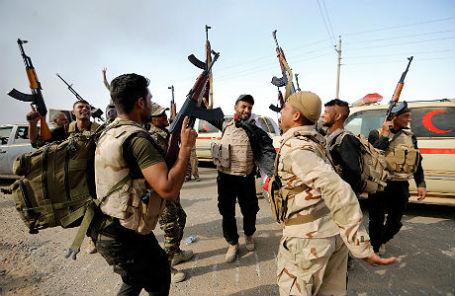 Члены иракских сил безопасности празднуют освобождение села от боевиков «Исламского государства» к югу от Мосула.