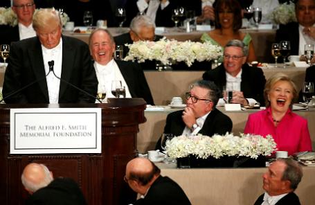 Хиллари Клинтон (справа) смеется над шуткой Дональда Трампа (за трибуной).