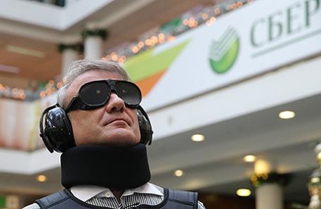 Глава Сбербанка Герман Греф в специализированном костюме GERT, имитирующем разные виды физических ограничений, во время проверки системы продуктов и сервисов для людей с ограниченными возможностями в одном из отделений Сбербанка.