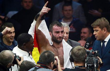 Российский боксер Мурат Гассиев (в центре) после победы в поединке против российского боксера Дениса Лебедева.