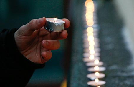 Человек зажигает свечу у здания концертного зала «Александровский» в память о погибших во время крушения самолета ТУ-154. Москва, Россия, 25 декабря 2016.