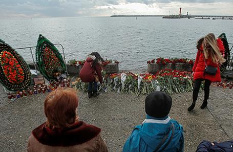 Люди возлагают цветы в память о погибших при крушении Ту-154 недалеко от места катастрофы. Сочи, Россия.