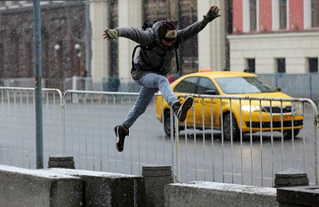 Молодой человек прыгает по бетонным блокам, установленным на Тверской улице в целях безопасности.