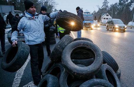 Протестующие активисты на окраине Киева собирают покрышки, чтобы их поджечь.