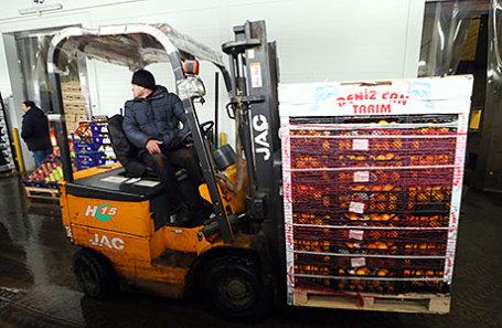 Разгрузка фруктов из Турции на территории оптово-продовольственного центра.