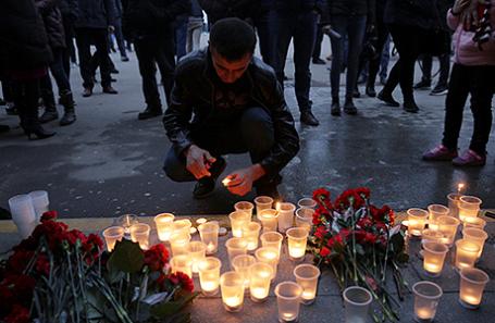 Люди зажигают свечи в  память о жертвах теракта у станции метро «Спасская» в Санкт-Петербурге.