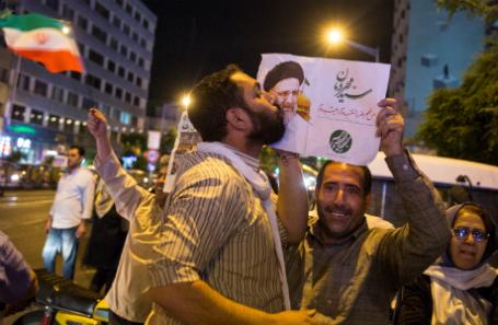Иран, 17 мая 2017. Сторонник кандидата в президенты Ирана Ибрагим Раиси целует его плакат во время предвыборного митинга в Тегеране.