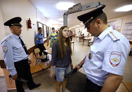 Проверка старшеклассницы на металлоискателе сотрудниками полиции.