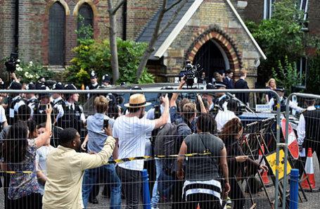 Полицейские защищают автомобиль с премьер-министром Британии Терезой Мэй от толпы родственников погибших при пожаре здания на Гренфелл-Тауэр.