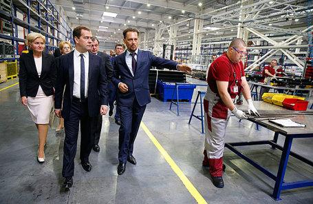 Премьер-министр Дмитрий Медведев и генеральный директор ООО «Серпуховский лифтостроительный завод» Виталий Шарипов (слева направо на первом плане) во время посещения Серпуховского лифтостроительного завода 9 июня 2014.