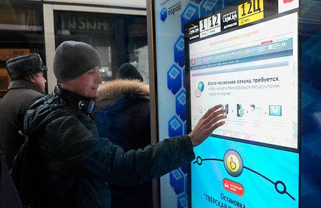Пассажир во время использования сервиса на интерактивной остановке на улице Тверская.