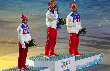 Российские спортсмнены Максим Вылегжанин, завоевавший серебряную медаль, Александр Легков, завоевавший золотую медаль, Илья Черноусов (слева направо), завоевавший бронзовую медаль в масс-старте на 50 км на соревнованиях по лыжным гонкам среди мужчин во время медального награждения на торжественной церемонии закрытия XXII зимних Олимпийских игр.