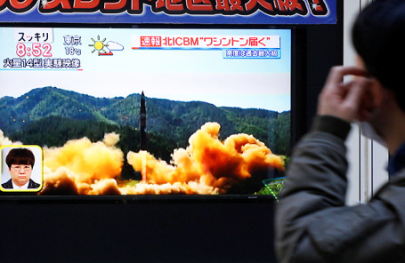Житель Японии смотрит новости о запуске новой ракеты в Северной Корее.