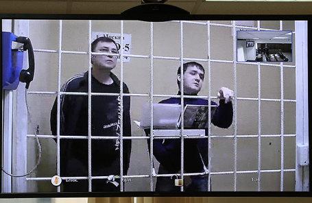 Фигуранты дела о поставке крупной партии аргентинского кокаина в Россию Владимир Калмыков и Иштимир Худжамов (слева направо на экране монитора) во время рассмотрения жалобы в Мосгорсуде на продление их ареста, 12 марта 2018.