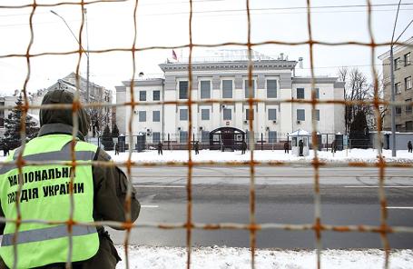 Сотрудник Национальной гвардии Украины у оцепленного здания посольства РФ в Киеве.