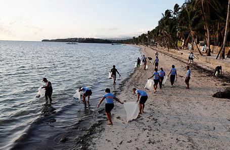 Полицейские собирают мусор на пляже Булабог острова Боракай в первый день временного закрытия для туристов.