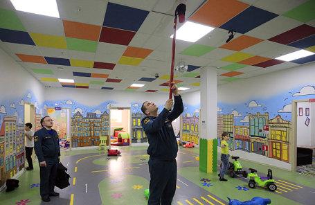 Сотрудник МЧС России во время проверки дымовых и газовых извещателей и системы пожаротушения в торговом центре.