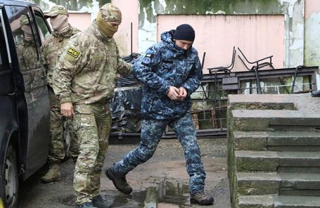 Сотрудник ФСБ России сопровождает задержанного украинского моряка на судебное заседание в Симферополе.