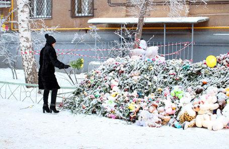 Жительница города возлагает цветы в память о погибших на месте обрушения подъезда жилого дома №164 на проспекте Карла Маркса в Магнитогорске.