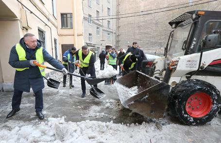 Врио губернатора Санкт-Петербурга Александр Беглов (слева) и глава администрации Петроградского района Санкт-Петербурга Иван Громов (в центре) во время уборки снега на одной из улиц Санкт-Петербурга.