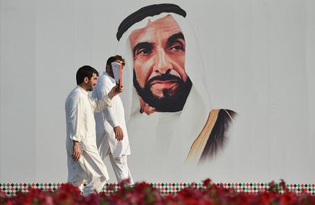 Повседневная жизнь в Абу-Даби. На плакате: эмир Абу-Даби и президент ОАЭ Халифа ибн Зайд Аль Нахайян.