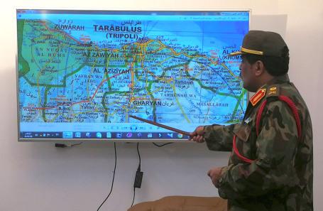 Представитель Ливийской национальной армии полковник Ахмед Аль-Мисмари указывает на карту Ливии во время пресс-конференции в Бенгази.