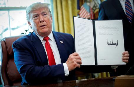 Дональд Трамп демонстрирует распоряжение о введении санкций в отношении Ирана.
