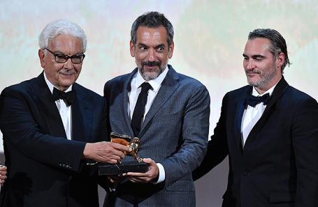 Президент Венецианской биеннале Паоло Баратта и режиссер Тодд Филлипс держат главный приз фестиваля — Золотого льва