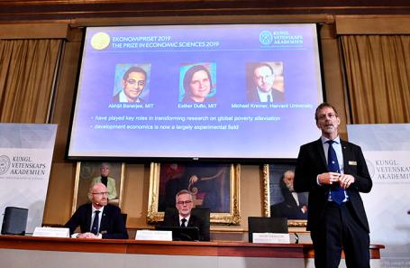 На экране слева направо: Абиджит Банерджи, Эстер Дюфло и Майкл Креймер.