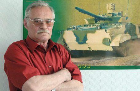Александр Благонравов на фоне плаката с изображением БМП-3.