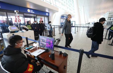 Измерение температуры пассажиров в аэропорту Уханя.