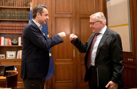 Приветствие, заменяющее рукопожатие. Премьер Греции Кириакос Мицотакис и глава Европейского фонда финансовой стабильности Клаус Реглинг (справа).