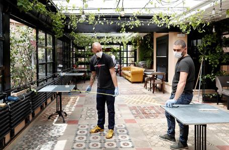 Сотрудники ресторана в Риме готовятся к открытию.