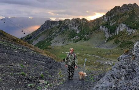 Сотрудник МЧС с собакой во время поисковой операции группы из 11 туристов, пропавших в воскресенье в горах под Сочи.