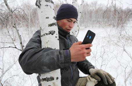Студент из деревни Станкевичи Алексей Дудоладов ловит интернет на березе.