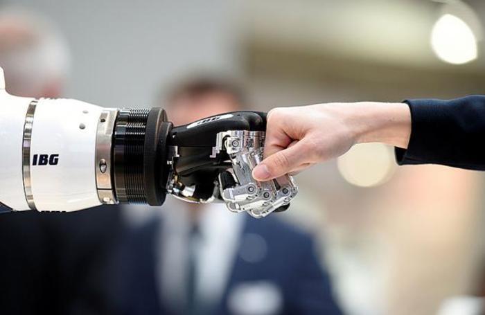 Посетитель и робот-гуманоид на промышленной выставке Hannover Messe в Ганновере, Германия.