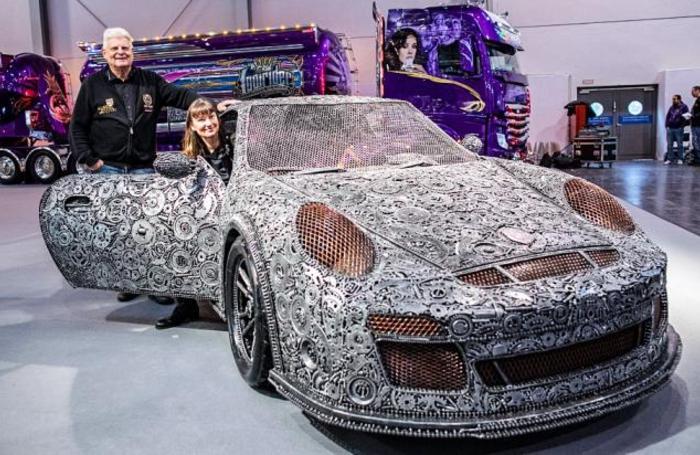 Владельцы автомобиля Porsche GT3 RS, собранного из 20 тысяч металлических деталей, на автосалоне Essen Motor Show. Германия.
