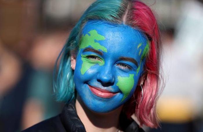 Одна из участниц демонстрации против жизнедеятельности человека, повлекшей изменение климата. Лондон, Великобритания.