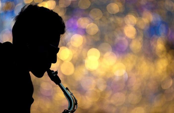 Музыкант играет на саксофоне на Никольской улице в Москве.