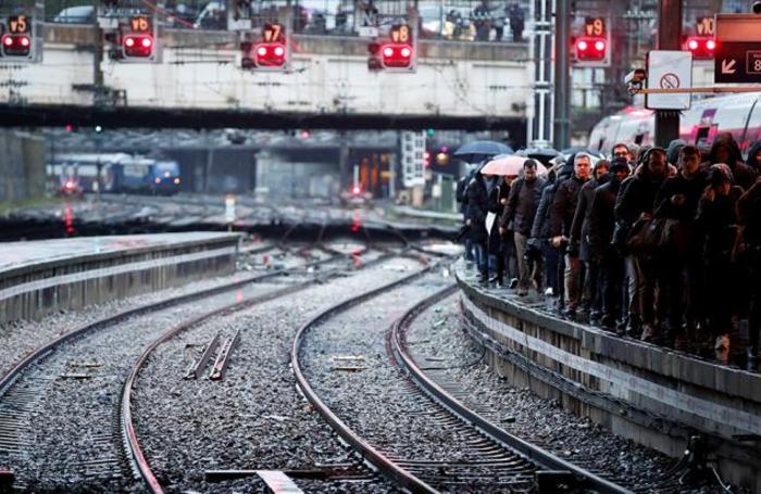 Пассажиры на платформе вокзала  Сен-Лазар в Париже. Транспортная система Франции парализована из-за забастовок против пенсионной реформы.