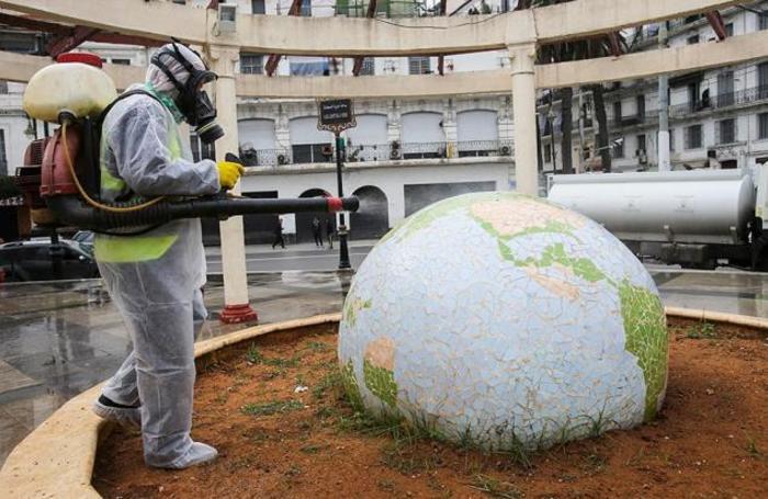 Сотрудник санэпидемслужбы дезинфицирует скульптуру в сквере жилого квартала в Алжире.
