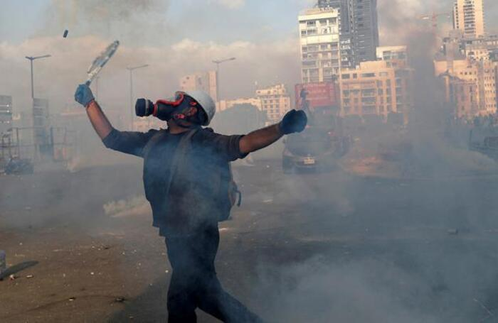 Участник демонстрации в Бейруте отбивает гранату со слезоточивым газом теннисной ракеткой.