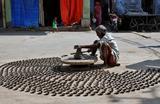Мужчина делает глиняные лампы, которые используются для украшения храмов и домов во время индуистского праздника Дивали, на улице в Аджмер, Индия.