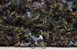 Рабочий едет мимо инсталляции в виде сложенных общественных велосипедов на свободной площадке в Сямэнь, провинция Фуцзянь, Китай.