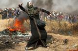 Девушка бросает камни в знак протеста во время столкновений палестинцев с израильскими войсками 13 апреля 2018 года..