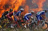Участники шестого этапа Тур-де-Франс проезжают мимо пожара во Франции.